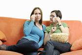 Zwei junge frau essen popcorn auf orange sofa — Stockfoto