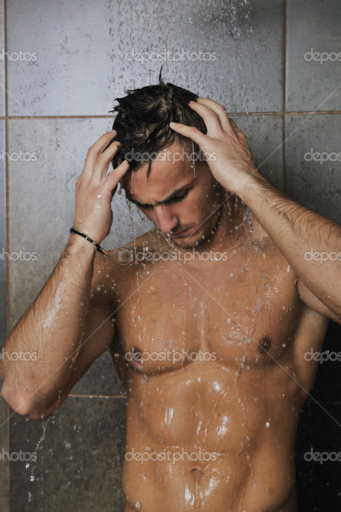 Young good looking and attractive man with muscular body wet taking shower in bath with black tiles in background  Stock Photo #3369323