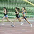 Girls running on athletics race track - ストック写真
