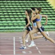 Girls running on athletics race track - Foto Stock