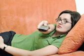 Ung kvinna koppla av på orange soffa — Stockfoto