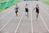 Girls running on athletics race track — Stock Photo