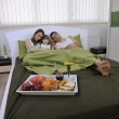 Happy family relaxing in bed — Stock Photo