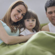 Stock Photo: Happy family relaxing in bed
