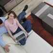 Young couple working on laptop at home — Стоковая фотография