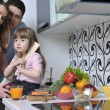 Happy young family in kitchen — Stock Photo