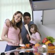 Happy young family in kitchen — Stok fotoğraf