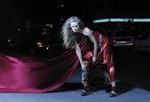 Elegant woman on city street at night — Stock Photo