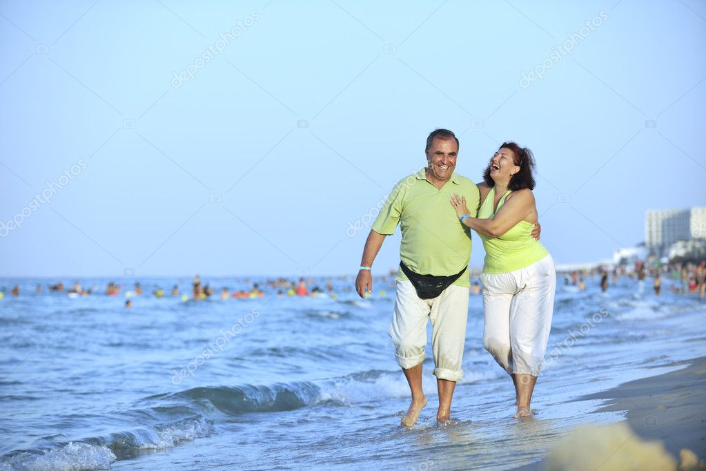 Happy senior mature elderly couple have romantic time on beach at sunset — Stock Photo #3564007