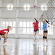 Girls playing volleyball indoor game — Stock fotografie