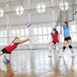 Stock Photo: Girls playing volleyball indoor game