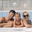Happy young family have fun on swimming pool - Stock Photo