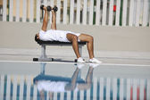 Young healthy athlete man exercise at poolside — Stock Photo