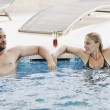 Stock Photo: Happy cople relaxing at swimming pool