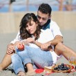 Stock Photo: Young couple enjoying picnic on the beach