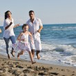 Happy family playing with dog on beach — Stock Photo #4359178
