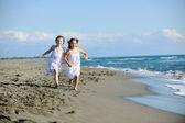 Cute little girls running on beach — Stock Photo