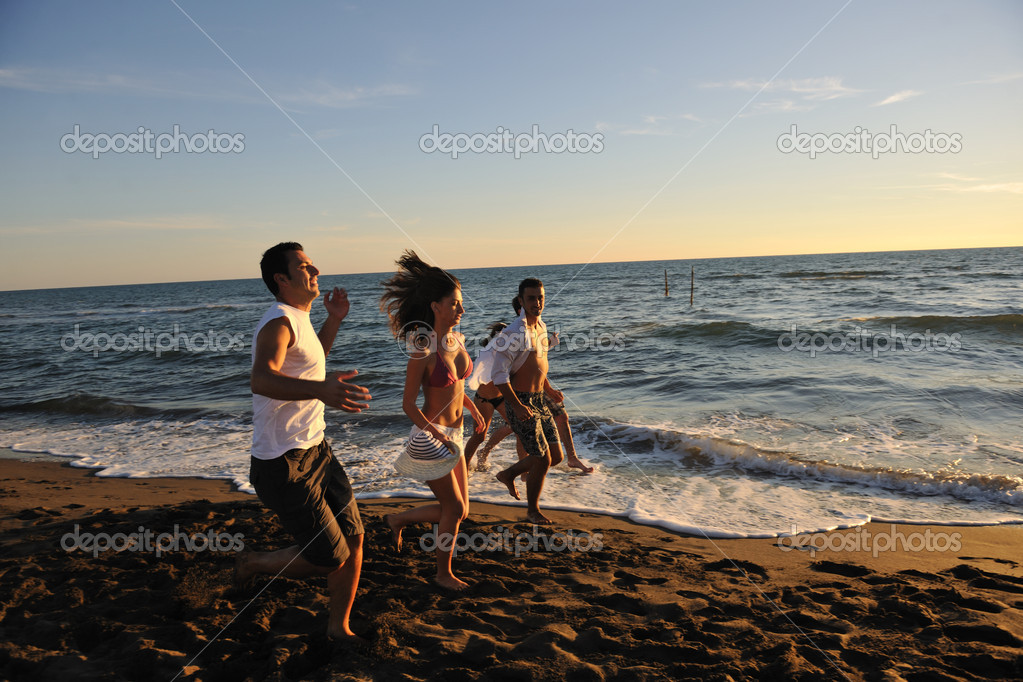 Happy young group have fun white running and jumping on beacz at sunset time — Stock Photo #4359978