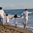 Happy family playing with dog on beach — Stock Photo #4361243