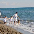 Happy family playing with dog on beach — Stock Photo #4361413