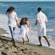 Happy family playing with dog on beach — Stock Photo #4361452