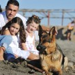 Happy family playing with dog on beach — Stock Photo