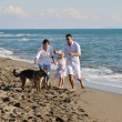 Happy family playing with dog on beach — Stock Photo #4361898