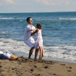 Happy family playing with dog on beach — Stock Photo #4361992