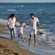 Happy family playing with dog on beach — Stock Photo #4362102