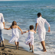 Happy family playing with dog on beach — Stock Photo #4362218