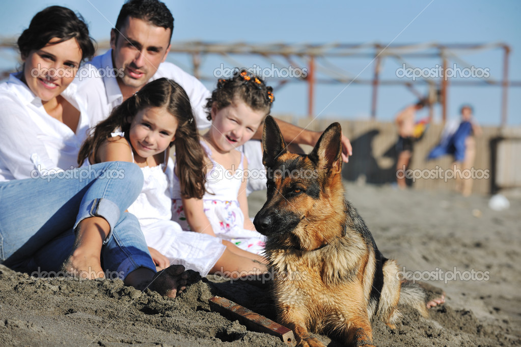 Happy young family in white clothing have fun and play with beautiful dog at vacations on beautiful beach  — Stock Photo #4361853