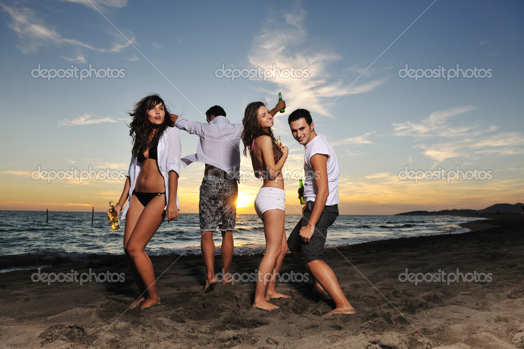 Happy young friends group have fun and celebrate while jumping and running on the beach at the sunset — Foto de Stock   #4363623