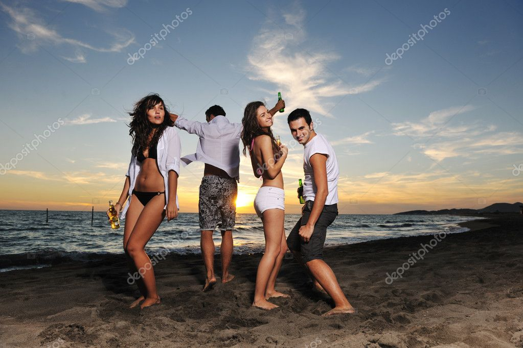 Happy young friends group have fun and celebrate while jumping and running on the beach at the sunset — Lizenzfreies Foto #4363623