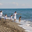 Happy family playing with dog on beach — Stockfoto