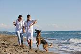 Glückliche familie mit hund am strand spielen — Stockfoto