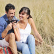 Happy couple enjoying countryside picnic in long grass — Stock Photo #4382030