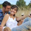 Happy couple enjoying countryside picnic in long grass — Stock Photo #4382158