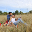 Happy couple enjoying countryside picnic in long grass — Stock Photo #4382198