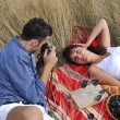 Happy couple enjoying countryside picnic in long grass — Stock Photo #4382222