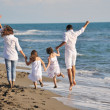 Happy young family have fun on beach — Stock Photo #4386312