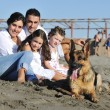 Happy family playing with dog on beach — Stock Photo #4387310
