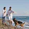Happy family playing with dog on beach — Stock Photo #4387626