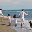 Happy family playing with dog on beach — Stock Photo #4387932