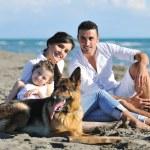 famiglia felice di giocare con il cane sulla spiaggia — Foto Stock