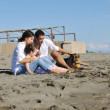 Happy family playing with dog on beach — Foto de stock #4388890