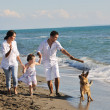 Happy family playing with dog on beach — Stock Photo #4388952