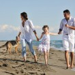 Happy family playing with dog on beach — Foto de Stock