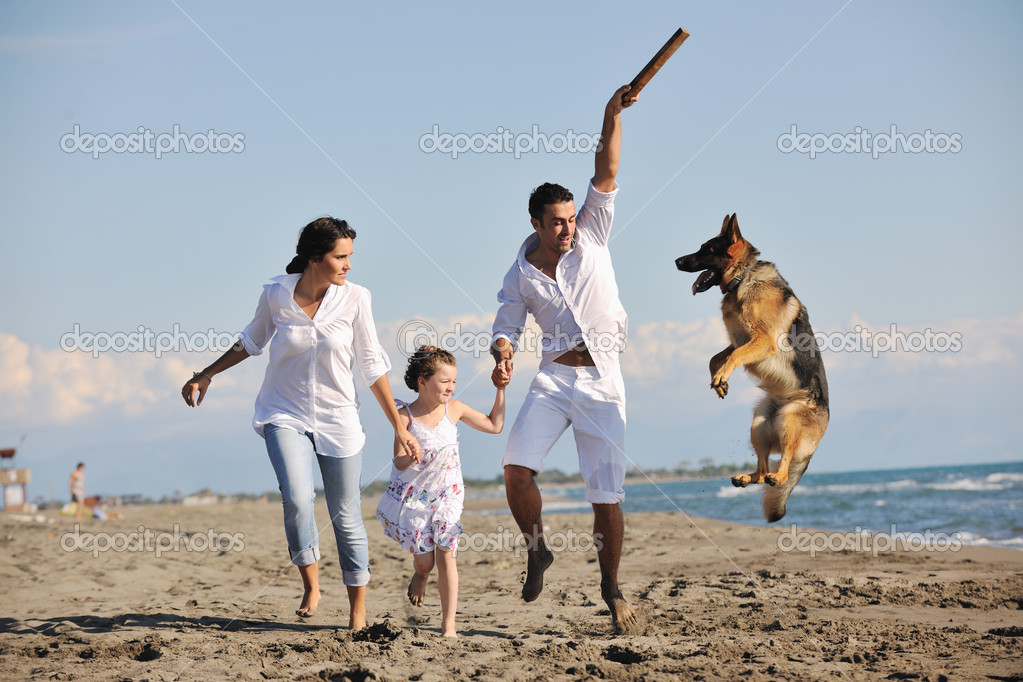 Happy young family in white clothing have fun and play with beautiful dog at vacations on beautiful beach  — Foto Stock #4388964