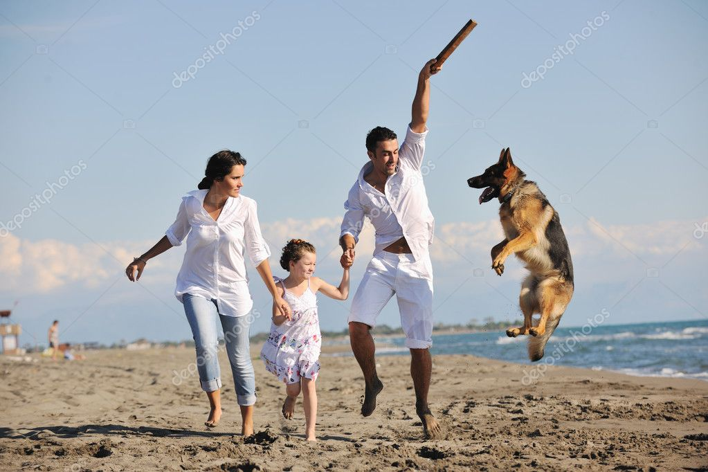 Happy young family in white clothing have fun and play with beautiful dog at vacations on beautiful beach  — Stok fotoğraf #4388964