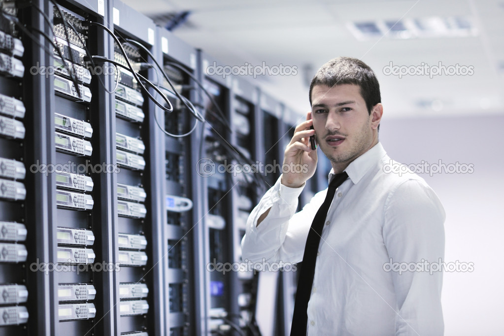 Young business man computer science engeneer talking by cellphone at network datacenter server room asking  for help and fast solutions and services — Stock Photo #4480615